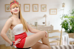 Beautiful girl in red shorts sitting on stool Stock Photography