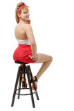 Beautiful girl in red shorts sitting on a stool Royalty Free Stock Image