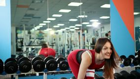 Beautiful girl in red suit makes lifting exercise dumbbell, which holds in hands. Woman is engaged in sports in gym. Concept of healthy lifestyle and stock video footage