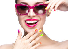 Beautiful girl in red sunglasses with bright makeup and colorful nails. Beauty face.