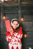 Beautiful girl in a red sweater wondering what inside christmas box - christmas and new year concept.  stock photography
