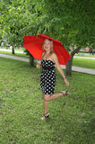 Beautiful girl with red umbrella laughs Stock Photo