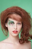 Beautiful girl in a red wig. The girl with an original make-up and a red wig. Fashion Stock Images