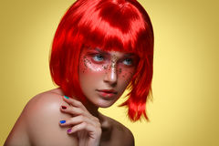Beautiful girl in red wig. Beautiful young woman with glowing skin, fashion make-up and metallic nails in short red wig touching hair. Beauty shot on yellow Stock Image