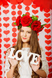 Beautiful girl in red wreath of flowers with the word love Stock Photo