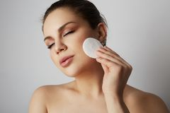 Beautiful girl refreshing skin face with white cotton pads over gray studio background.Model with light nude make-up. Healthcare skin makeup concept stock images