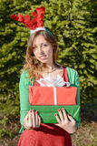 Beautiful  girl with reindeer ears holding Christmas presents Stock Images