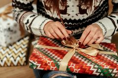 Beautiful girl in reindeer winter sweater unwrapping christmas p. Resent with golden ribbon, hands close-up, greeting card concept Royalty Free Stock Photography