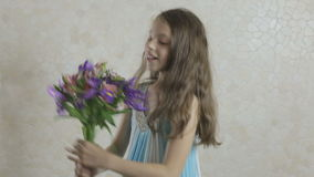 Beautiful girl rejoices donated bouquet of flowers and swirls. stock footage
