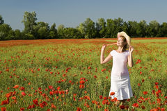 Beautiful girl relaxed. A beautiful woman feels happy on the poppy field stock photo