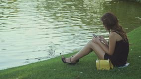 Beautiful girl relaxes on grass near pond with phone stock video footage