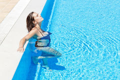 Beautiful girl relaxes in the pool. In the summer outs Stock Photography