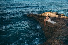 Beautiful girl relaxes on the rock on the coast ocean Stock Photo