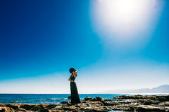 Beautiful girl relaxes on the rock on the coast sea Royalty Free Stock Images