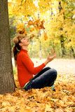 Beautiful girl relaxing. Autumn beautiful girl relaxing and playing wuth leafs Royalty Free Stock Images
