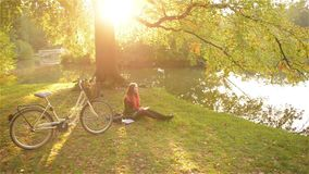 Beautiful girl relaxing in autumn park reading book, sitting on the grass near lake with her bicycle. Sunny day stock footage