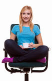 Beautiful girl relaxing in chair holds a cup of tea or coffee. Royalty Free Stock Image