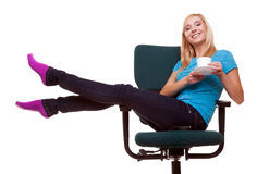 Beautiful girl relaxing in chair holds a cup of tea or coffee. Royalty Free Stock Photography