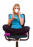 Beautiful girl relaxing in chair holds a cup of tea or coffee. Royalty Free Stock Images