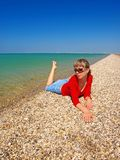 Beautiful girl relaxing on a coastline Royalty Free Stock Photo