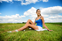 Beautiful girl relaxing in a green field royalty free stock photo