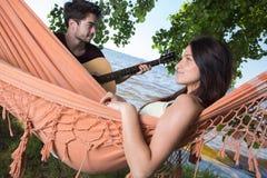 Beautiful girl relaxing in hammock listening boyfriend playing guitar Royalty Free Stock Photography