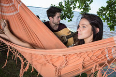 Beautiful girl relaxing in hammock listening boyfriend playing guitar Royalty Free Stock Photography