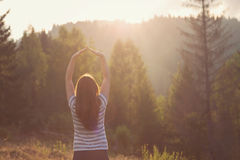 Beautiful girl, relaxing with her hands up. On the mountain, at sunset Royalty Free Stock Image