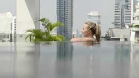 Beautiful girl is relaxing in an infinity pool stock video footage