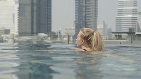 Beautiful girl is relaxing in an infinity pool stock footage