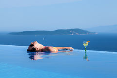 Beautiful girl is relaxing in an infinity pool. With a great view Stock Images