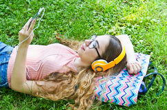Beautiful girl relaxing and listen music in the headphones in th Stock Photos
