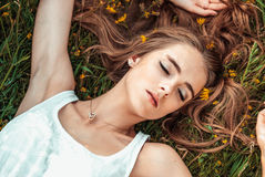 Beautiful girl is relaxing and lying on the grass Stock Photos