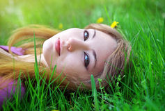 Beautiful girl relaxing lying on the grass Stock Photo