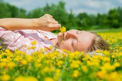 Happy woman lying on the field in grass with yellow flowers outdoors. Enjoy nature. Allergy free. Beautiful girl is relaxing lying on the grass in the meadow royalty free stock images