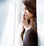 Beautiful girl relaxing near window. Dark long  curly hair Stock Image