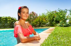 Beautiful girl relaxing at outdoor swimming pool stock photo