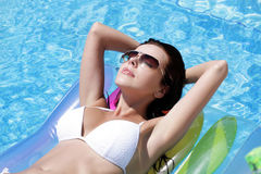 Beautiful girl relaxing in pool. Lying on mattress Stock Photography