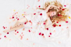 Beautiful girl is relaxing in rose petals Stock Photo