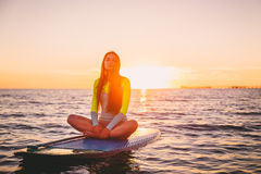 Beautiful girl relaxing on stand up paddle board, on a quiet sea with warm sunset colors. Stock Image