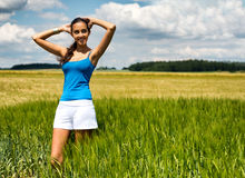 Beautiful girl relaxing in a summer wheat field Royalty Free Stock Image