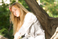 Beautiful girl relaxing on a tree Stock Photography
