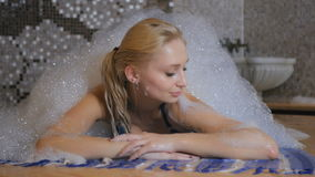 Beautiful girl relaxing under the foam in the Turkish bath. Beautiful girl laying on the carpet in the Turkish bath. Young girl is smiling and relaxing under the stock footage