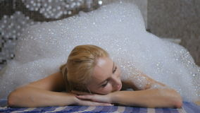 Beautiful girl is relaxing under the foam in the Turkish bath. Beautiful girl lays the head on the hands and laying on the carpet in the Turkish bath. Young girl stock footage