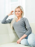Beautiful girl relaxing on a white sofa at home Stock Photography
