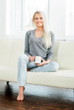 Beautiful girl relaxing on a white sofa at home and drinking tea Royalty Free Stock Photos