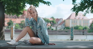 Beautiful girl relaxing on wooden bench in a city park. Happy stylish girl wearing denim jacket enjoying time during sunny day stock footage