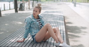 Beautiful girl relaxing on wooden bench in a city park. Happy stylish girl wearing denim jacket enjoying time during sunny day stock video