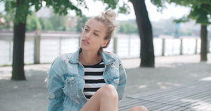 Beautiful girl relaxing on wooden bench in a city park. Happy stylish girl wearing denim jacket enjoying time during sunny day stock video footage