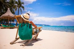 Beautiful girl relaxing in wooden chair beach at Royalty Free Stock Photos